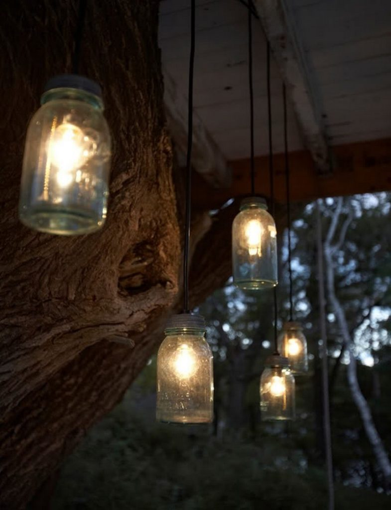 Reporposed mason jars become rustic lights hanging from underneath the treehouse.