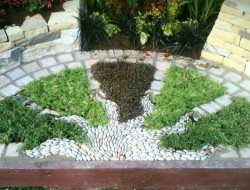 Radiating pebble sun mosaic with herbs (part of the gold awarded show garden at the 2012 Harrogate Autumn flower show) — at Harrogate Flower Show.