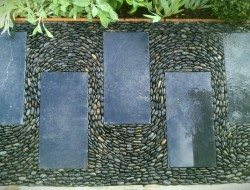 Swirly pebble mosaic path, black limestone paving and polished black pebbles (gold award winning show garden at the 2012 Harrogate Spring flower show) — at Harrogate Flower Show.