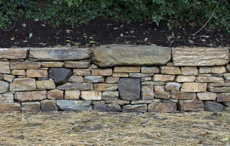 Building a dry stone retaining wall is well within your abilities. This is a great example of a retaining wall that does NOT interfere with the natural site drainage.