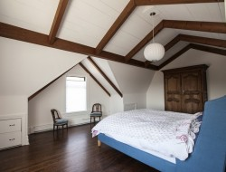 On the top floor, the master bedroom caries the style of the rest of the house with its dark stained floors, white walls and mix of modern and vintage elements.