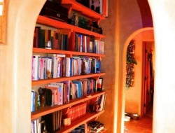 H and H Straw Bale Home - hall lined with bookshelves