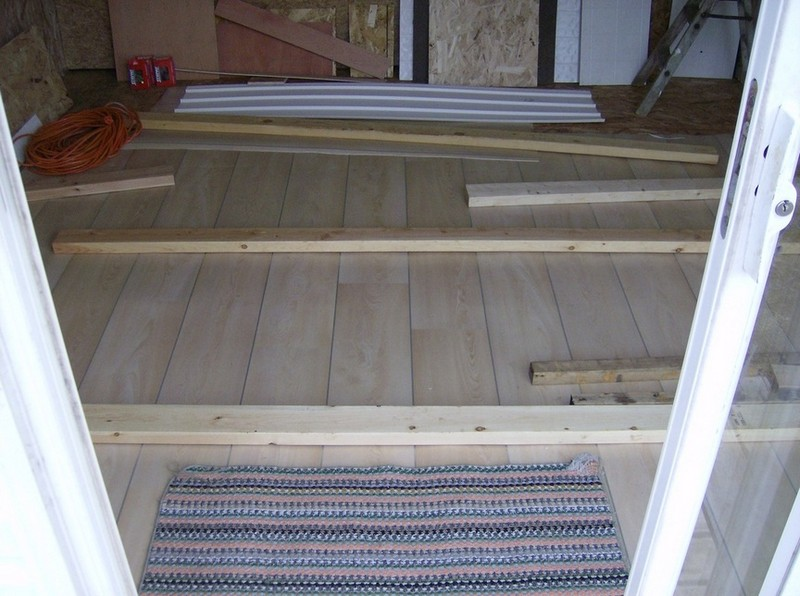How To Build A DIY Pallet Shed - Putting linoleum on the floor