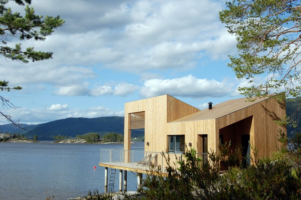 Nisser Micro Cabin stands on stilts above the water and partially on land.