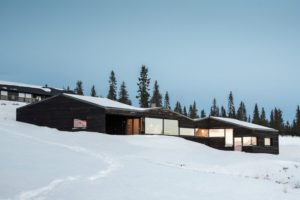 Cabin Sjusjøen's black facade stands out against the stark white backdrop.