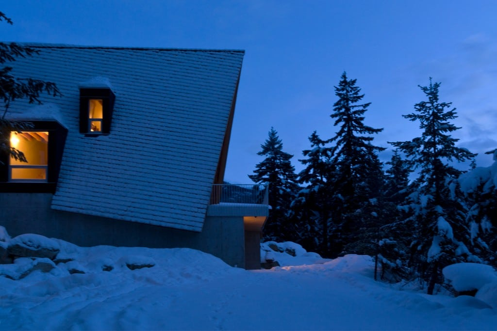 A wooden shingle roof tops Whistler Cabin, an A-frame mountain retreat.