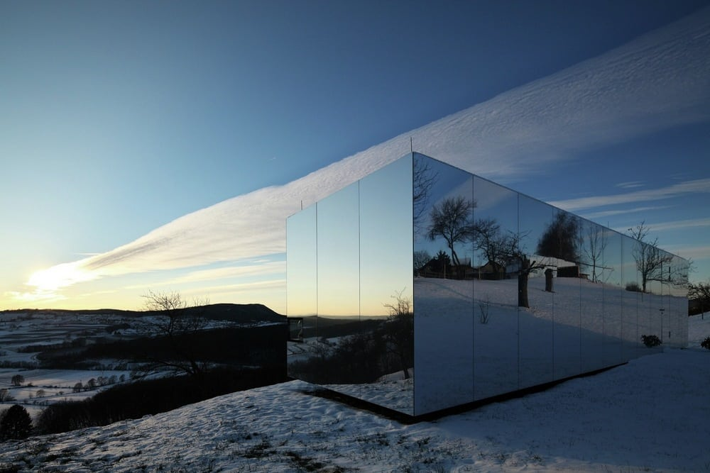 The reflective facade of Casa Invisible allows it to blend seamlessly well with its environment.