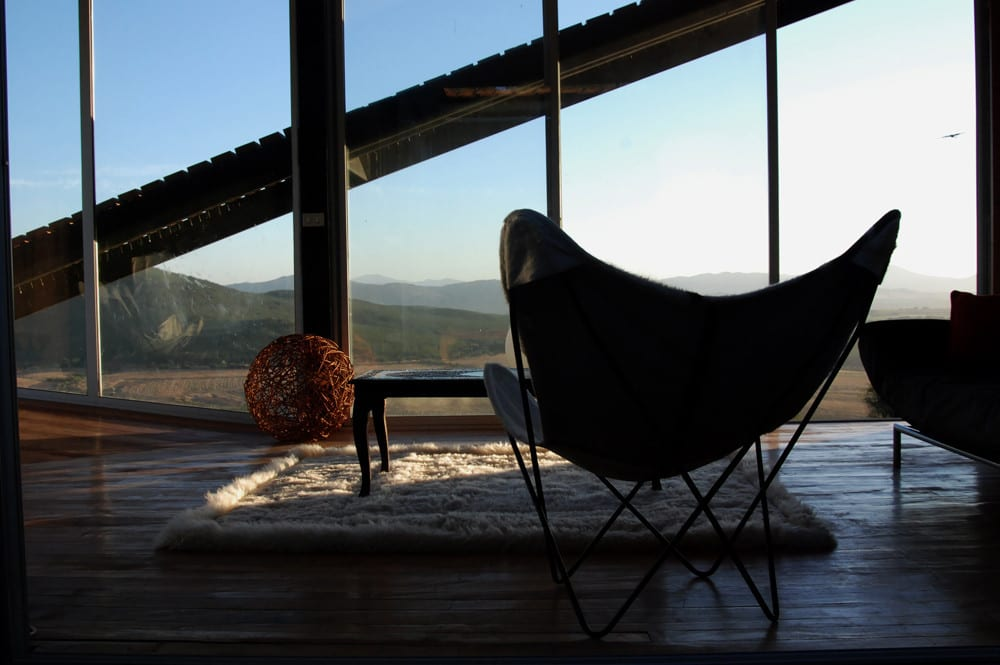 Large windows provide sweeping views of the surrounding Chilean mountains.