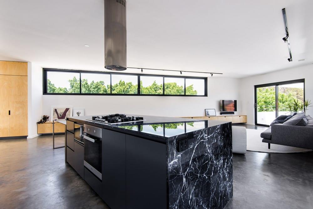 Bright white walls and dark floors provide a striking yet elegant contrast.